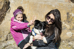Beautiful young women laughing and  hugging dog. Happy friends   hugging dog outdoor Stock Photo