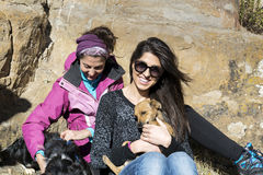 Beautiful young women laughing and  hugging dogs. Happy friends   hugging dogs outdoor Royalty Free Stock Photo