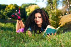 Beautiful young women lie on a grass with book Royalty Free Stock Images