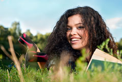 Beautiful young women lie on a grass with book Stock Image