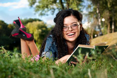 Beautiful young women lie on a grass with book Stock Images