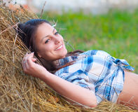 Beautiful young women lies on the pile of hay Stock Photos