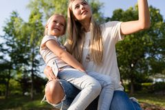 Beautiful young mother and daughter with blonde hair embracing outdoor. Stylish girls making walking in the park. Family concept stock photo