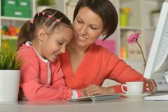 Woman and little girl using computer Stock Images