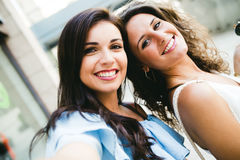 Beautiful young women looking at camera in the street. Stock Photo