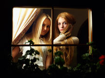Beautiful young women looks from window at night. Two beautiful young women looking from window at night royalty free stock photography