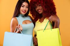 Happy afro american and asian women at shopping holding bags isolated on orange background on black friday holiday. Beautiful young women make shopping in black Royalty Free Stock Image