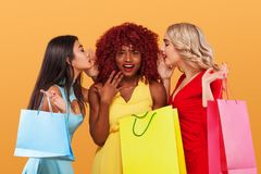 Three happy women after shopping. Afro american, asian and caucasian races. Shopping with isolated on orange background. Beautiful young women make shopping in Stock Image