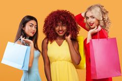 Three happy women. Afro american, asian and caucasian races. Shopping with isolated on orange background on black friday Royalty Free Stock Photo