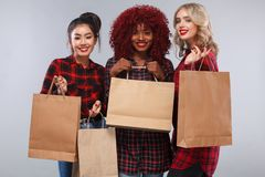 Three women at shopping on Black Friday holiday. Beautiful young women make shopping in black friday holiday. Girls with bag on lgiht background Royalty Free Stock Photos