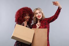 Two women at shopping on Black Friday holiday. Beautiful young women make shopping in black friday holiday. Girls with bag on lgiht background Royalty Free Stock Images
