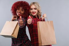 Two women at shopping on Black Friday holiday. Beautiful young women make shopping in black friday holiday. Girls with bag on lgiht background Stock Photos