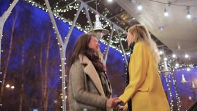 A beautiful young women.meeting and hugging the skyline and lights. Night meeting stock footage