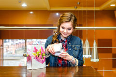 Beautiful young women opens and joyfully looks in a gift box Royalty Free Stock Images