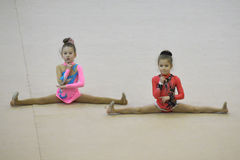 Beautiful young women performing floor exercise during gymnastics competition Royalty Free Stock Images
