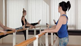 Beautiful young women performing splits stretching in the rehearsal room. Slender girls stand in front of the mirror and stock video