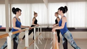 Beautiful young women performing splits stretching in the rehearsal room. Slender girls stand in front of the mirror and stock footage