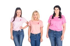 Women in pink t-shirts with ribbons. Beautiful young women in pink t-shirts with ribbons smiling at camera isolated on white Stock Photography