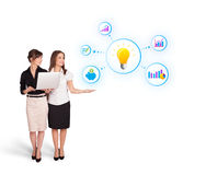 Beautiful young women presenting light bulb with colorful graphs Royalty Free Stock Image