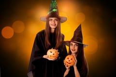 Beautiful young women with pumpkins in hands. In halloween style posing in studio stock photo