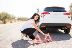 Woman placing warning triangle by broken car. Beautiful young women putting red emergency stop triangle signs on the road with broken car Stock Image