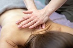 Beautiful young woman is receiving a massage at a massage salon royalty free stock photography