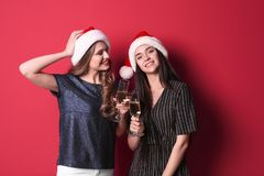 Beautiful young women in Santa hats with glasses of champagne on color background. Christmas celebration royalty free stock images