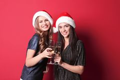 Beautiful young women in Santa hats with glasses of champagne on color background. Christmas celebration royalty free stock photography