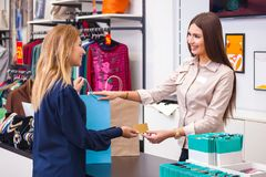 Young woman with shopping bag giving her credit card to seller i Stock Images