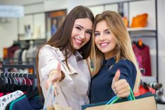 Beautiful young women with shopping bags showing thumbs up. Beautiful young women with shopping bags looking happy and showing thumbs up Royalty Free Stock Photos