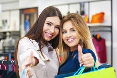 Beautiful young women with shopping bags showing thumbs up. Beautiful young women with shopping bags looking happy and showing thumbs up Royalty Free Stock Photography