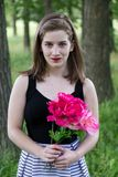 Beautiful young women in sleeveless dress holding bouquet. Vertical frontal medium shot of beautiful young woman in sleeveless dress holding bouquet with soft royalty free stock photo