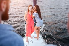 Beautiful young women stand together and pose. They wispering and laughing. Men stands adn look at them. Women are on. Bow of yacht royalty free stock image