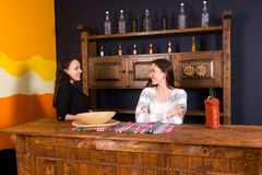 Beautiful young women standing at bar counter in Mexican pub. A shelf with spicy sauces in the background Stock Photography