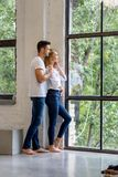 Young couple hugging. A beautiful young women standing next to the window with boyfriend hugging her from behind Royalty Free Stock Photos