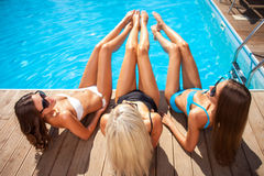 Beautiful young women are sunbathing near water Royalty Free Stock Images