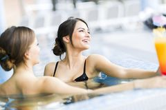 Beautiful young women in a swimming pool. Beautiful young women talking and relaxing in a swimming pool Stock Photography