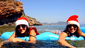 Beautiful young women are swimming in the sea with christmas hat stock video