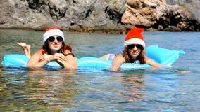 Beautiful young women are swimming in the sea with christmas hat stock video footage