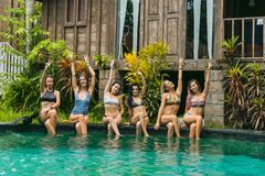 Beautiful young women in swimwear sitting at swimming pool and smiling. At camera stock photography