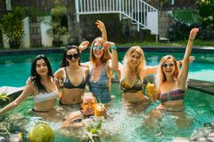 Beautiful young women in swimwear and sunglasses smiling at camera while having fun together at swimming. Pool stock images