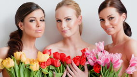 Beautiful young women with tulips. Three beautiful women with bunches of fresh spring tulips held to their chests smiling at the camera, head and shoulders stock video
