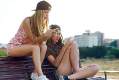 Beautiful young women using mobile phone in the street. Stock Image