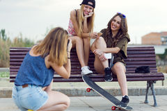 Beautiful young women using mobile phone in the street. Stock Photography