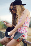 Beautiful young women using mobile phone in the street. Royalty Free Stock Image