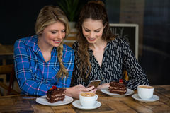 Beautiful young women using smart phone in cafe. Beautiful young woman using smart phone with dessert and coffee cups on table in cafe Royalty Free Stock Photo