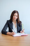 Beautiful young women is using a smart phone and making notes while sitting at desk. Young woman is using a smart phone and making notes while sitting at desk Stock Image