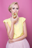 Beautiful young women with yellow blouse taste yellow dessert. Fashion shot. Soft colors Royalty Free Stock Image