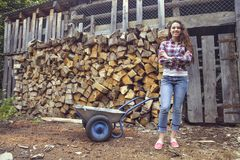 Beautiful youngcountry  woman on firewood background Royalty Free Stock Photo