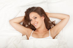 Beautiful youngwoman in white bedding Royalty Free Stock Photography